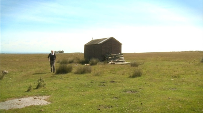 Alan Watson beside a small shed with reedy plants all around to the horizon
