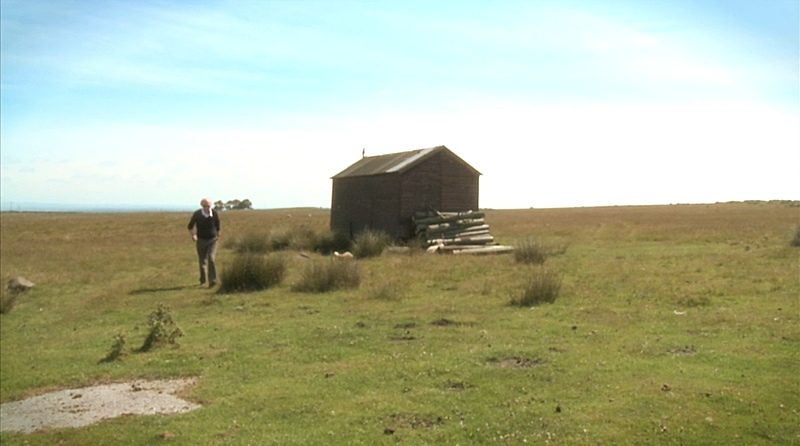 Alan Watson walks past a small wooden shed in the vast expanse of moorland, Haverah Park