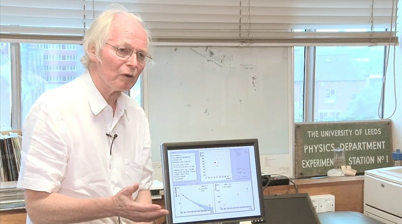 Alan sits on a desk explaining cosmic rays with computer behind and old objects