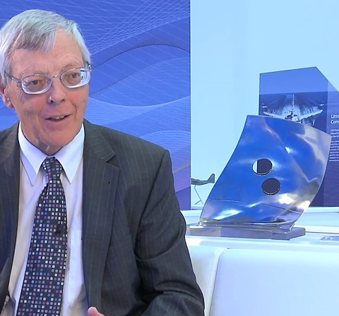 Close-up of Mike Howse with turbine models behind him
