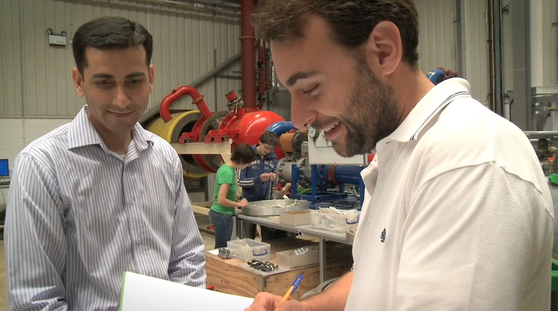 Two students discuss a logbook with turbines behind them