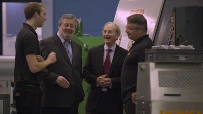 John Deer and Sir David McMurtry discussing production with employees at the Renishaw New Mills site.